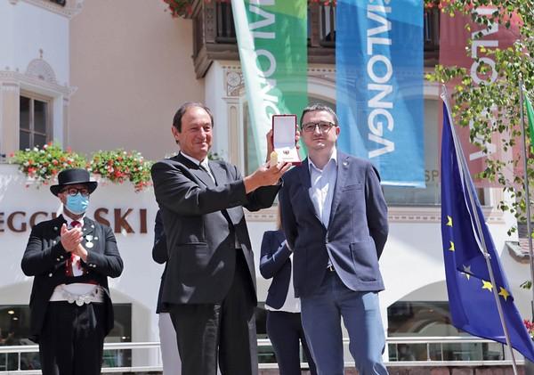 Angelo Corradini di Marcialonga mostra l'Aquila consegnata da Maurizio Fugatti